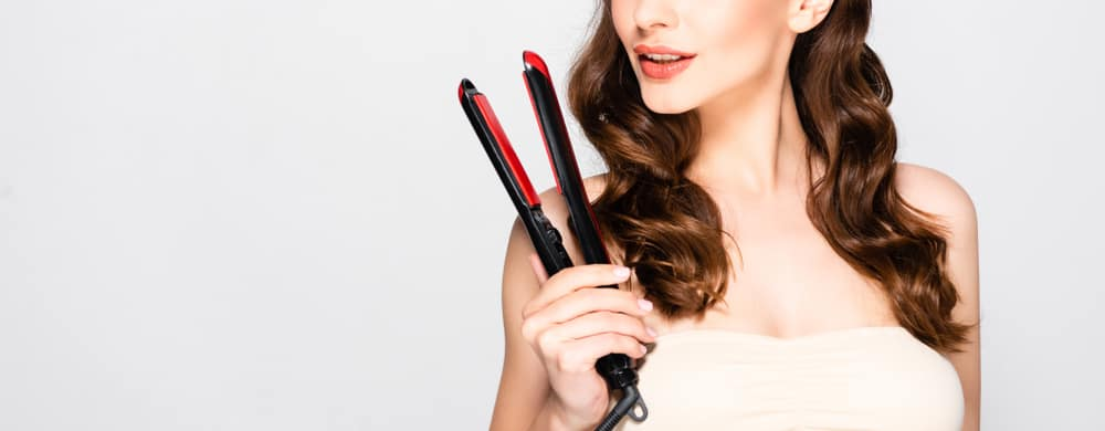 curly hair model holding flat iron in his hand